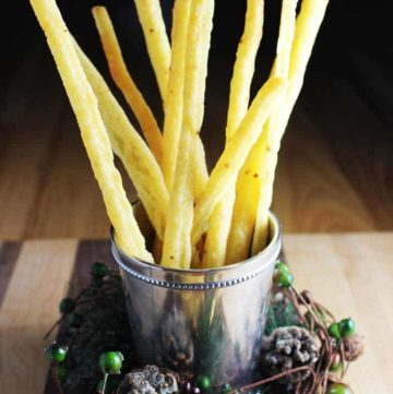 Easy cheese straws standing up in a festive glass with pinecones around it