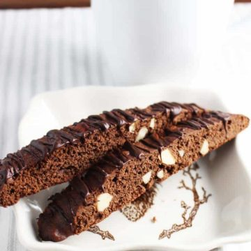 Two chocolate biscotti with almonds on a plate with a cup of coffee