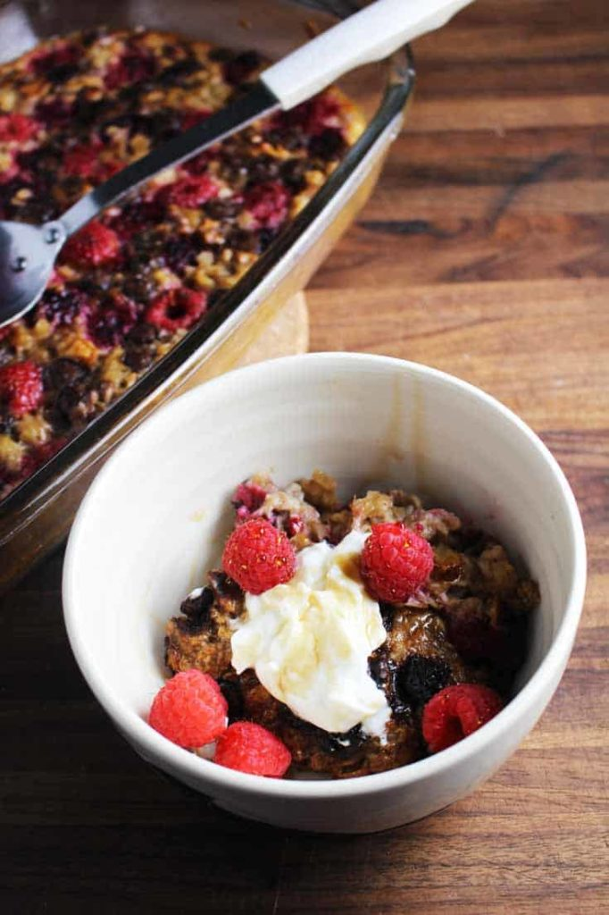 Raspberry dark chocolate baked oatmeal in a bowl with yogurt and fresh raspberries