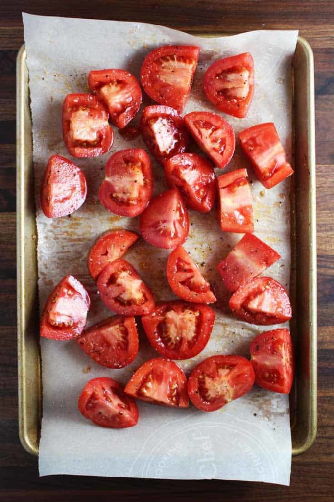 Quarted raw tomatoes on a parchment-lined sheet pan, ready for roasting for caprese chicken recipe.