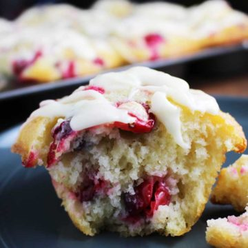 Fresh cranberry orange muffin with a cream cheese drizzle, torn in half and on a plate.