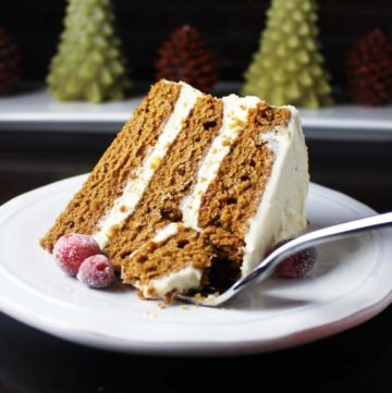 Slice of gingerbread cake with brown butter cream cheese frosting on a plate, decorated with sugared cranberries