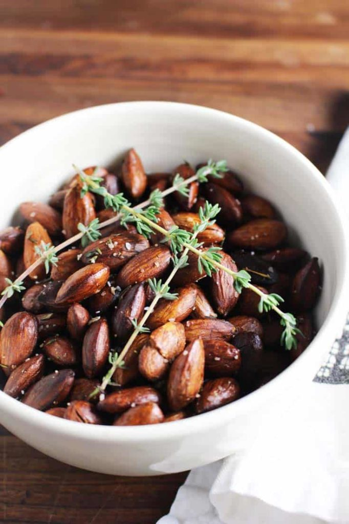 Closeup of roasted almonds in a bowl with thyme sprigs