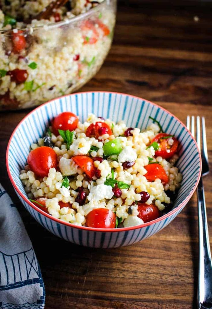 A bowl of Mediterranean Israeli couscous salad with a fork