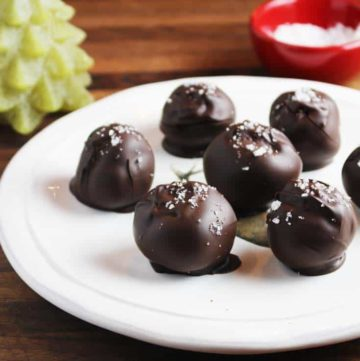 Seven Dark chocolate truffles with caramel, sprinkled with Fleur de sel, on a plate, with a Christmas tree candle in background