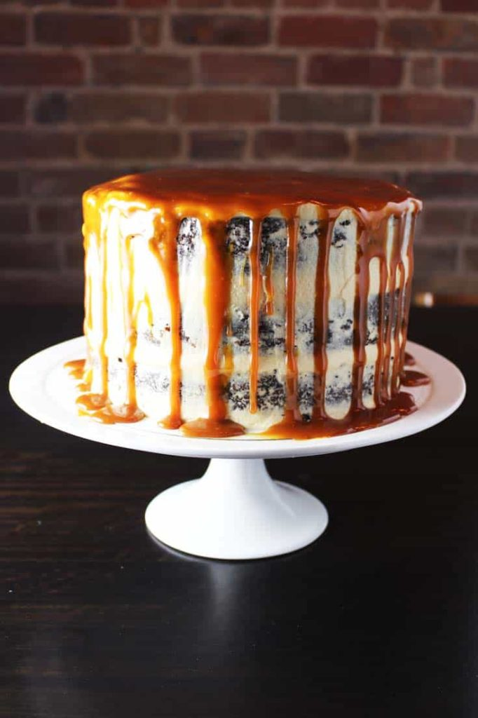 Caramel chocolate cake on a plate with coconut caramel frosting and caramel drizzle