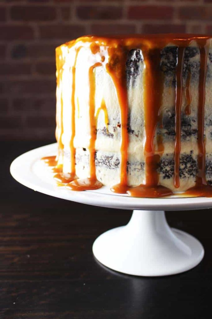 Closeup of caramel chocolate cake on a plate with coconut caramel frosting and caramel drizzle