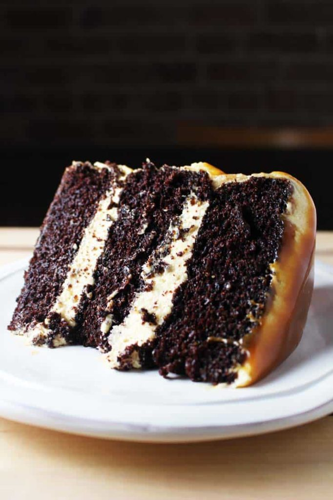 Slice of caramel chocolate cake on a plate with coconut caramel frosting and caramel drizzle