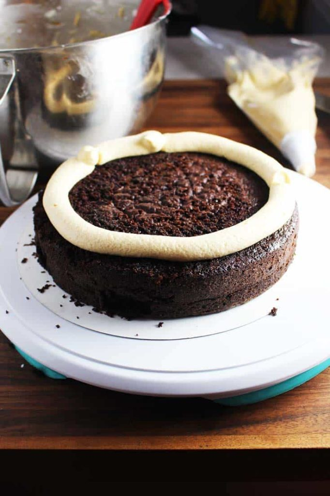 Chocolate cake layer with piped frosting dam - how-to for frosting a caramel chocolate cake