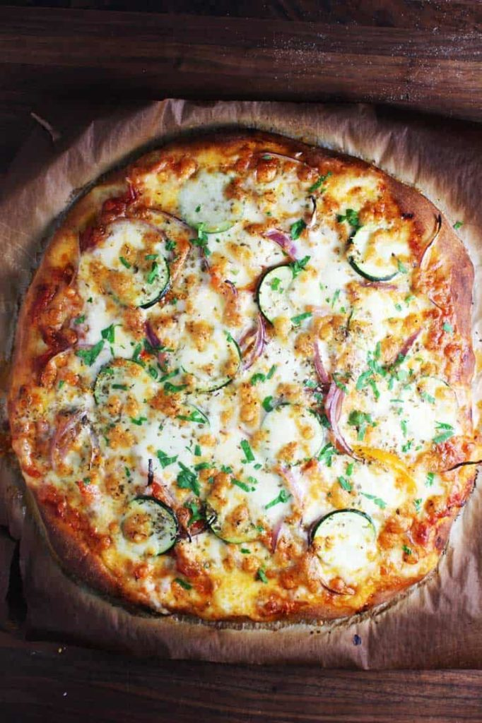 Overhead view of a veggie pizza recipe, baked and unsliced, on parchment paper