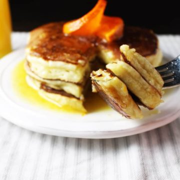 Ricotta pancakes with orange syrup on a plate with a forkful of pancakes in the foreground