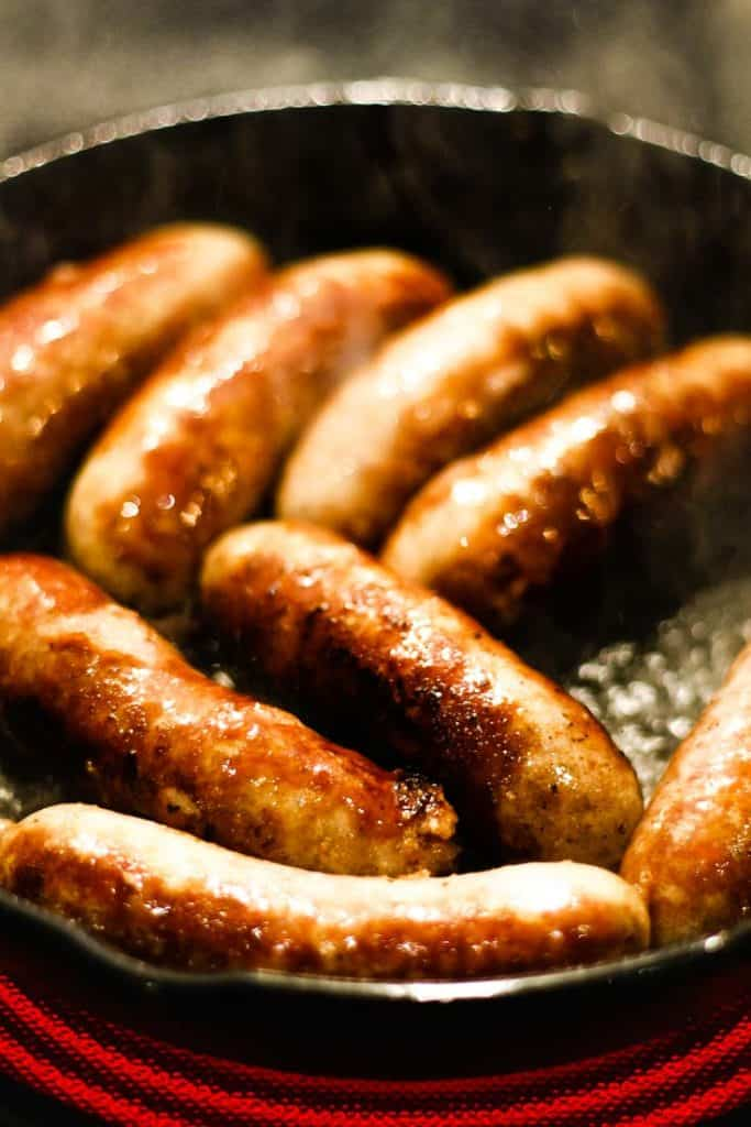 Sausages cooking in a cast iron pan