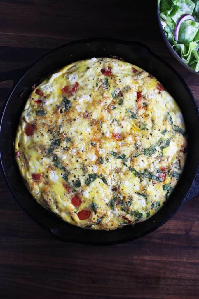 Overhead view of baked easy fritattata recipe in a cast iron pan