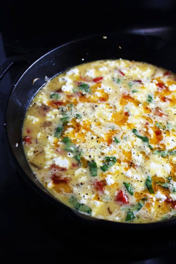 Unbaked ingredients for easy frittata recipe in a cast iron pan