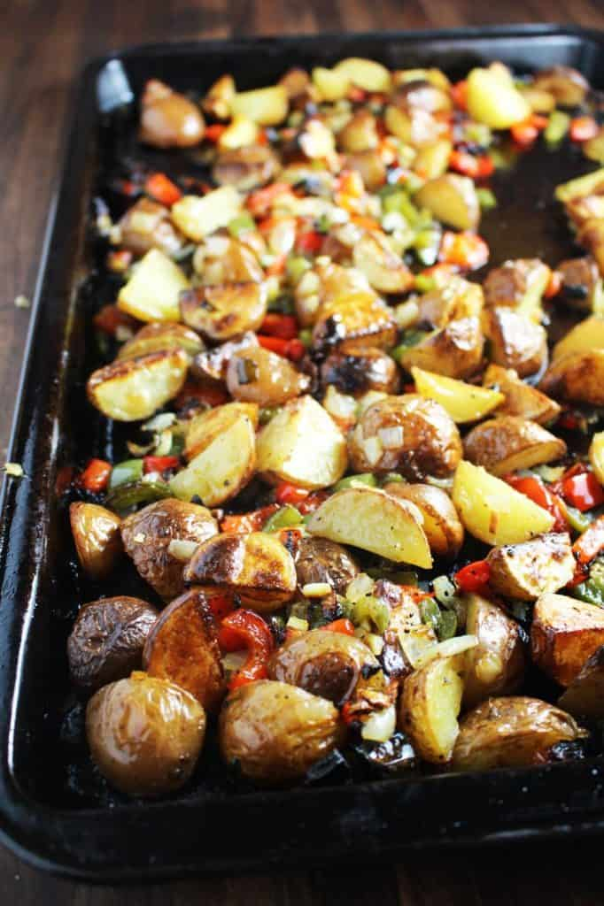 Potatoes, onions and bell peppers roasted on a pan for cheesy breakfast potatoes
