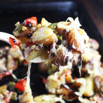 Cheesy breakfast potatoes being served from the pan with a spatula