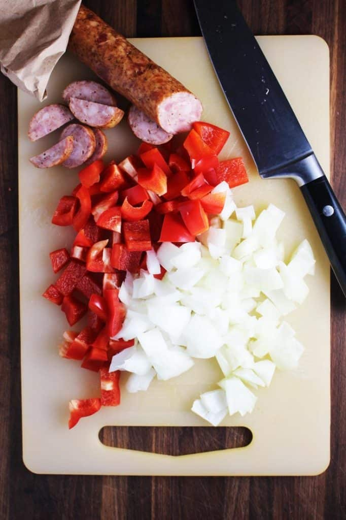 Chopped red bell pepper, onion and sausage on a cutting board for sausage and vegetable pasta skillet