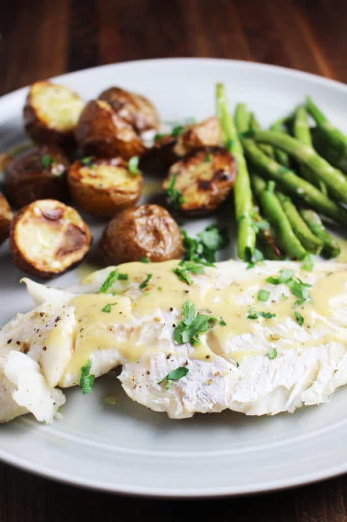 Close up view of white fish, green beans and potatoes from sheet pan dinner