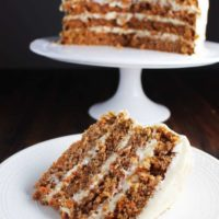 Slice of four layer carrot cake on a plate with cake on a stand in background.