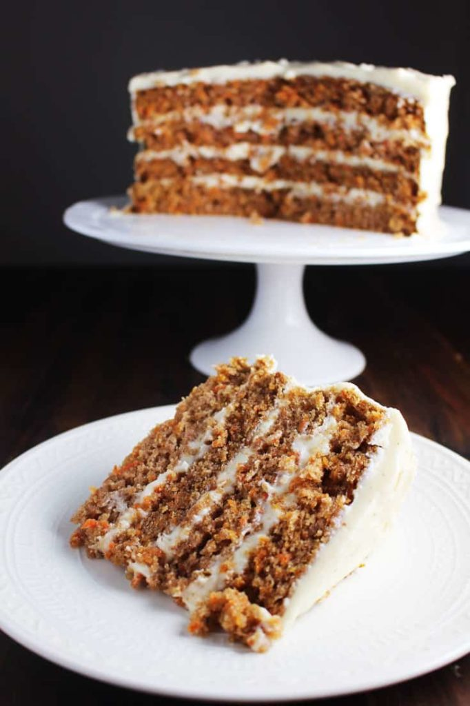 Slice of four layer moist carrot cake on a plate with cake on a stand in background.