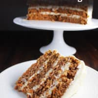 Slice of moist carrot cake on a plate with cake on a stand in the background