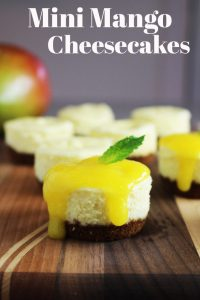 Mini cheesecakes with Biscoff crust and mango coulis on a wooden board