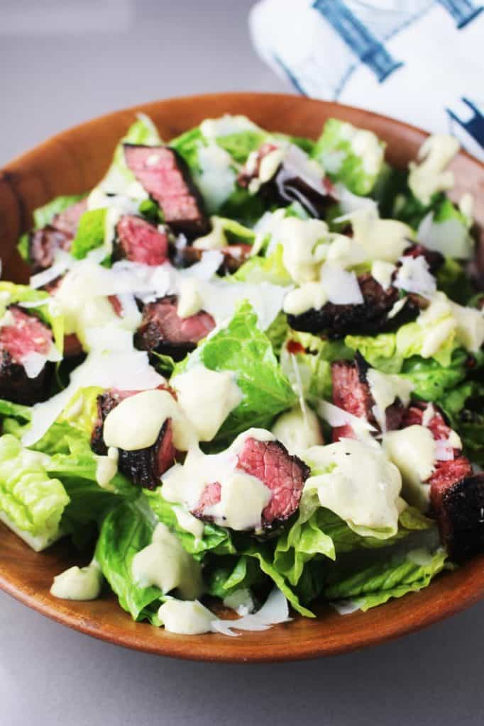 Caesar salad recipe with steak and croutons in a wooden bowl
