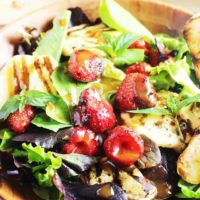 Grilled halloumi and strawberry salad in a wooden bowl