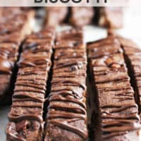chocolate almond biscotti drizzled with chocolate on parchment paper