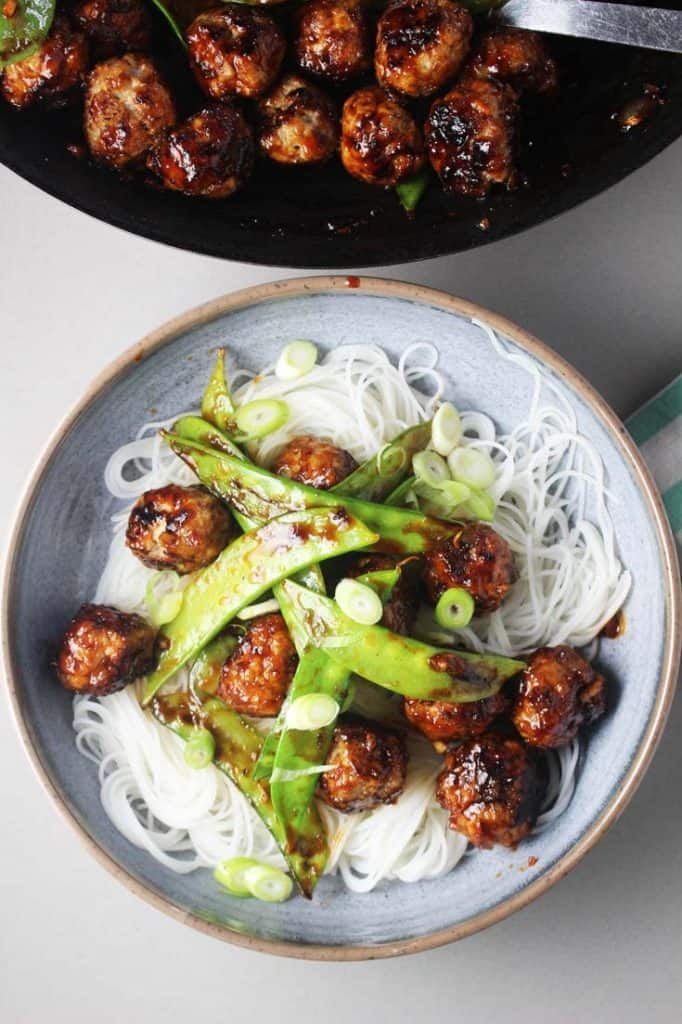 Asian meatballs with sriracha and honey sauce and snow peas in a bowl over rice noodles