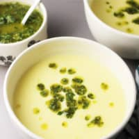 Fresh corn soup recipe in a bowl swirled with chimichurri
