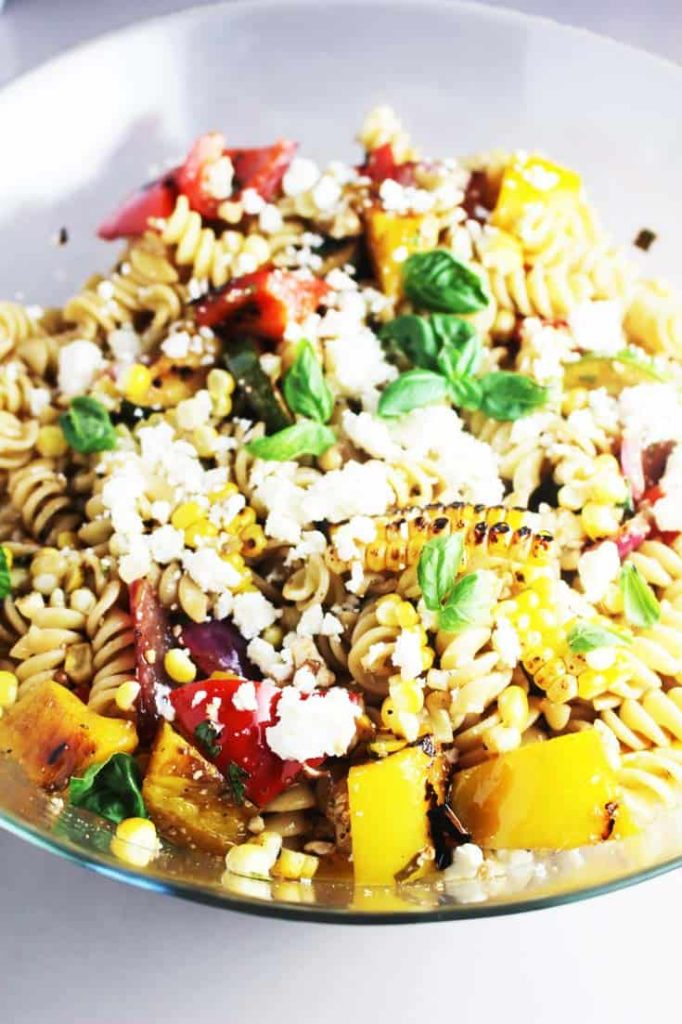 Summer pasta salad with grilled vegetables in a glass salad bowl