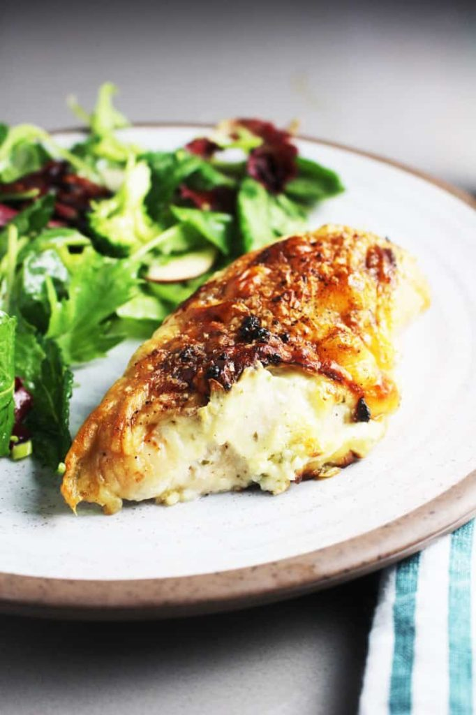 A Roasted chicken breast stuffed with Boursin cheese on a plate with salad