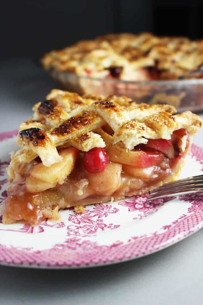 A slice of apple cranberry pie on a plate
