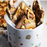 chocolate bark peices in a Christmas tin with wax paper