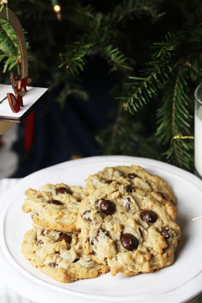 A plate of oatmeal chocolate chip cookies with peanut butter in front of a Christmas tree