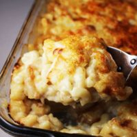 Baked macaroni and cheese in a glass baking dish with a portion scooped out
