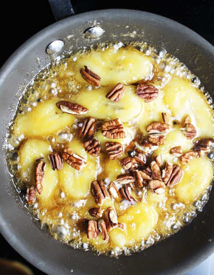Sliced bananas and pecans in a frying pan, being caramelized with butter and brown sugar for caramelized banana pecan oatmeal