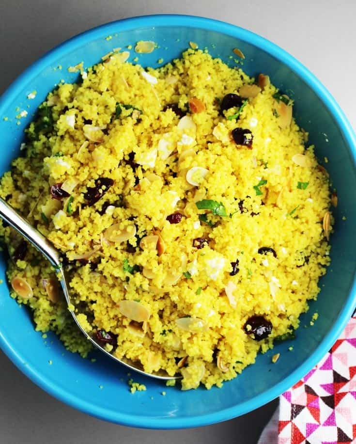 Overhead view of a large blue bowl of curried couscous salad