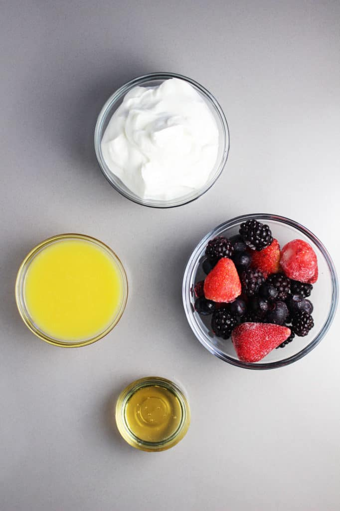 Ingredients to make triple berry greek yogurt smoothies in little glass bowls. Yogurt, orange juice, frozen berries and honey.