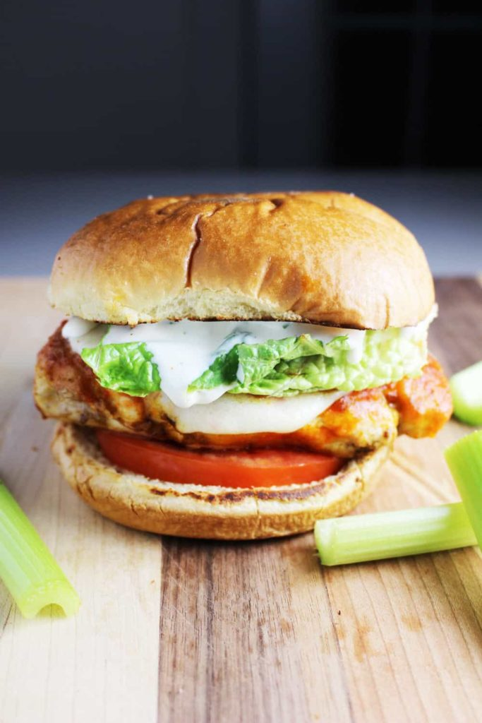 A Buffalo chicken burger topped with ranch dressing, tomato and lettuce on a wooden cutting board