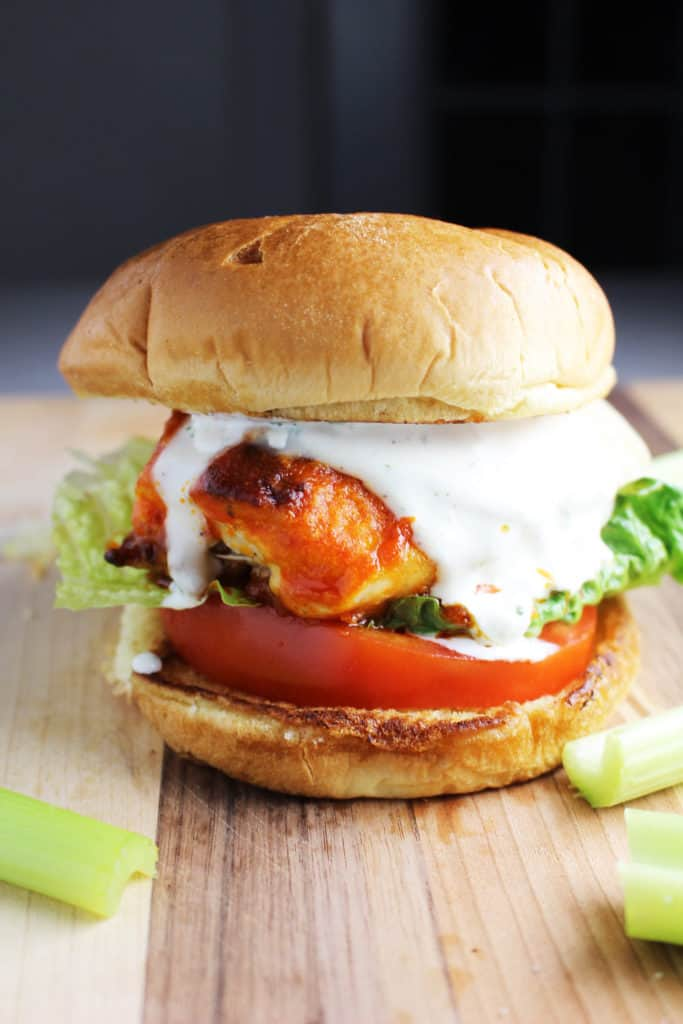 A Buffalo chicken burger with cheese, ranch, tomato and lettuce on a wooden cutting board