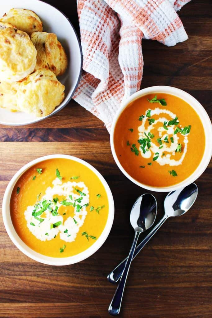 Two bowls of tomato soup garnished with cream and parsley and a bowl of biscuits