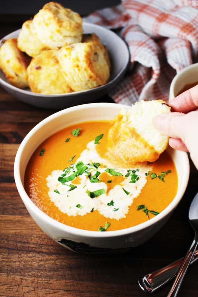 A bowl of tomato soup garnished with cream and parsley, with a biscuit being dipped into it.