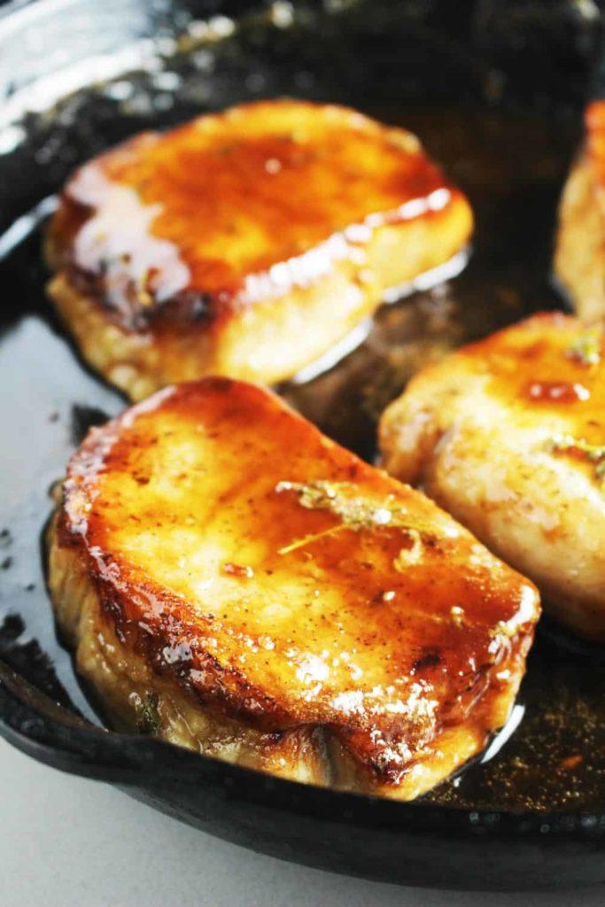 Boneless maple soy glazed pork chops in a cast iron pan