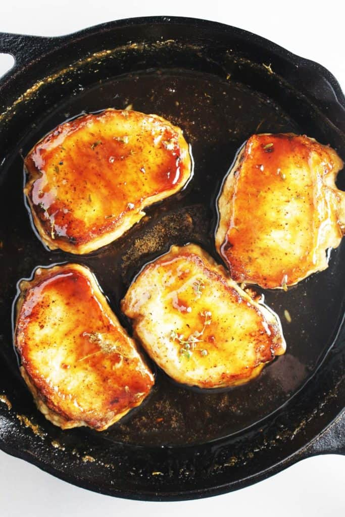 Overhead view of maple soy glazed pork chops in a cast iron skillet