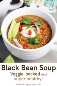 A bowl of vegetarian black bean soup garnished with avocado, sour cream, cilantro, lime and red pepper