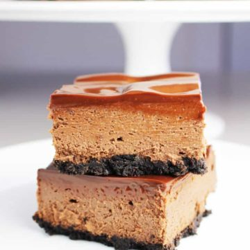 Two triple chocolate cheesecake bars stacked on top of one another on a white plate with more bars on a cake stand in the background