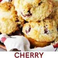 Sour cherry muffins with coconut streusel piled into a wooden bowl