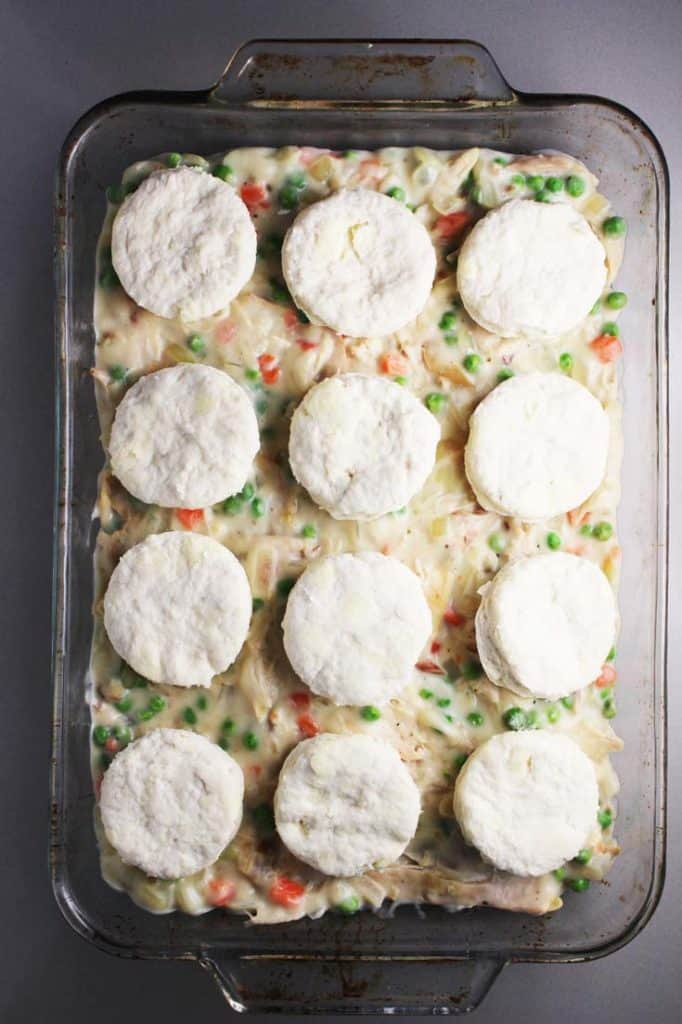 raw biscuits on top of unbaked chicken filling for chicken and biscuits